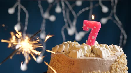 inflar : Birthday cake with 7 number burning pink candle and sparkler on blue backgraund. Slow motion and close-up view