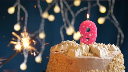 nove : Birthday cake with 9 number burning pink candle and sparkler on blue backgraund. Slow motion and close-up view