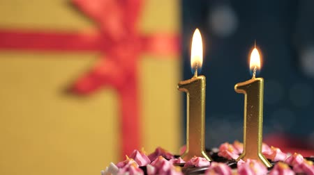 eleven people : Birthday cake number 11 golden candles burning by lighter, blue background gift yellow box tied up with red ribbon. Close-up and slow motion