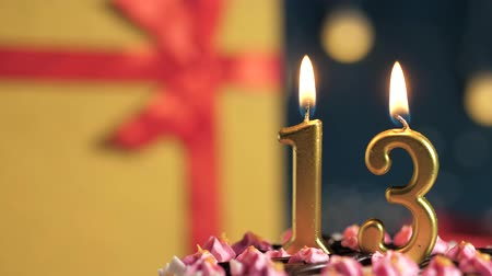 縛ら : Birthday cake number 13 golden candles burning by lighter, blue background gift yellow box tied up with red ribbon. Close-up and slow motion