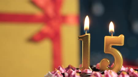 zapalovač : Birthday cake number 15 golden candles burning by lighter, blue background gift yellow box tied up with red ribbon. Close-up and slow motion Dostupné videozáznamy