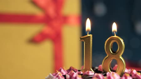 zapalovač : Birthday cake number 18 golden candles burning by lighter, blue background gift yellow box tied up with red ribbon. Close-up and slow motion