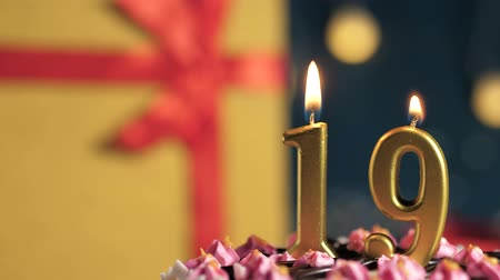 縛ら : Birthday cake number 19 golden candles burning by lighter, blue background gift yellow box tied up with red ribbon. Close-up and slow motion