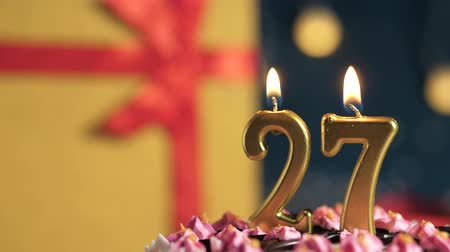 zapalovač : Birthday cake number 27 golden candles burning by lighter, blue background gift yellow box tied up with red ribbon. Close-up and slow motion Dostupné videozáznamy