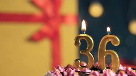 tied : Birthday cake number 36 golden candles burning by lighter, blue background gift yellow box tied up with red ribbon. Close-up and slow motion Stock Footage