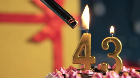 zapalovač : Birthday cake number 43 golden candles burning by lighter, blue background gift yellow box tied up with red ribbon. Close-up and slow motion Dostupné videozáznamy