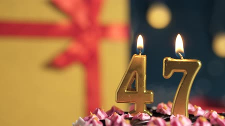 縛ら : Birthday cake number 47 golden candles burning by lighter, blue background gift yellow box tied up with red ribbon. Close-up and slow motion 動画素材