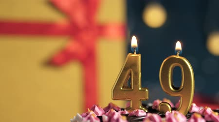 zapalovač : Birthday cake number 49 golden candles burning by lighter, blue background gift yellow box tied up with red ribbon. Close-up and slow motion