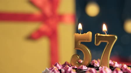 tied : Birthday cake number 57 golden candles burning by lighter, blue background gift yellow box tied up with red ribbon. Close-up and slow motion Stock Footage