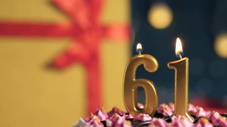 縛ら : Birthday cake number 61 golden candles burning by lighter, blue background gift yellow box tied up with red ribbon. Close-up and slow motion 動画素材