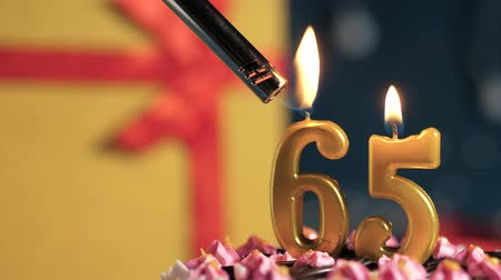 gyertyafény : Birthday cake number 65 golden candles burning by lighter, blue background gift yellow box tied up with red ribbon. Close-up and slow motion Stock mozgókép
