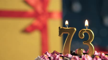 zapalovač : Birthday cake number 73 golden candles burning by lighter, blue background gift yellow box tied up with red ribbon. Close-up and slow motion