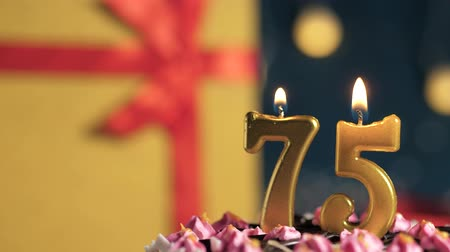 zapalovač : Birthday cake number 75 golden candles burning by lighter, blue background gift yellow box tied up with red ribbon. Close-up and slow motion