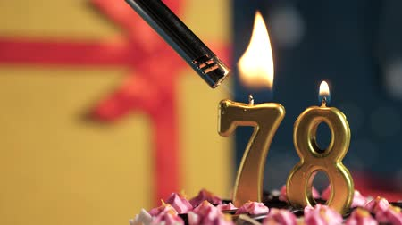 cigarette : Birthday cake number 78 golden candles burning by lighter, blue background gift yellow box tied up with red ribbon. Close-up and slow motion
