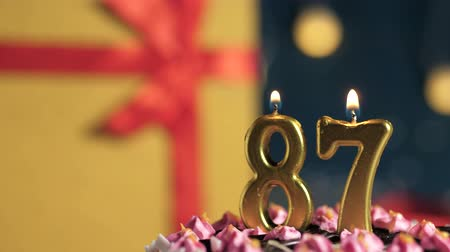 縛ら : Birthday cake number 87 golden candles burning by lighter, blue background gift yellow box tied up with red ribbon. Close-up and slow motion
