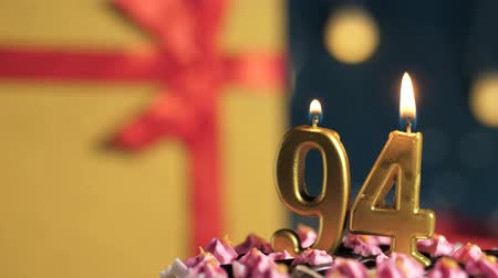 cigarette : Birthday cake number 94 golden candles burning by lighter, blue background gift yellow box tied up with red ribbon. Close-up and slow motion Stock Footage