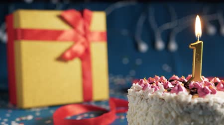 zapalovač : White birthday cake number 1 golden candles burning by lighter, blue background with lights and gift yellow box tied up with red ribbon. Close-up Dostupné videozáznamy