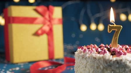 White birthday cake number 7 golden candles burning by lighter, blue background with lights and gift yellow box tied up with red ribbon. Close-up