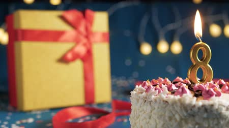 kek : White birthday cake number 8 golden candles burning by lighter, blue background with lights and gift yellow box tied up with red ribbon. Close-up