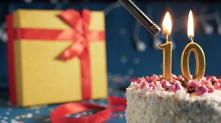 zapalovač : White birthday cake number 10 golden candles burning by lighter, blue background with lights and gift yellow box tied up with red ribbon. Close-up