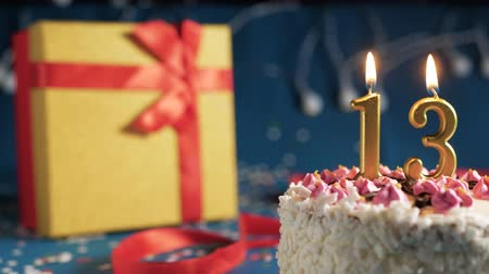 gyertyafény : White birthday cake number 13 golden candles burning by lighter, blue background with lights and gift yellow box tied up with red ribbon. Close-up Stock mozgókép
