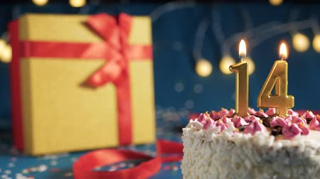 縛ら : White birthday cake number 14 golden candles burning by lighter, blue background with lights and gift yellow box tied up with red ribbon. Close-up 動画素材