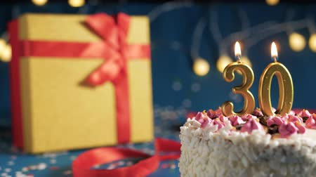 harminc : White birthday cake number 30 golden candles burning by lighter, blue background with lights and gift yellow box tied up with red ribbon. Close-up