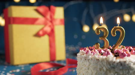 zapalovač : White birthday cake number 32 golden candles burning by lighter, blue background with lights and gift yellow box tied up with red ribbon. Close-up