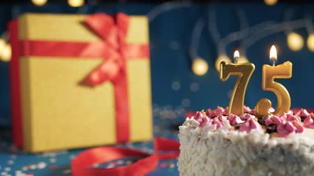 zapalovač : White birthday cake number 75 golden candles burning by lighter, blue background with lights and gift yellow box tied up with red ribbon. Close-up Dostupné videozáznamy