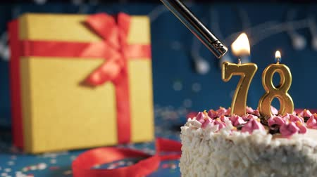 縛ら : White birthday cake number 78 golden candles burning by lighter, blue background with lights and gift yellow box tied up with red ribbon. Close-up