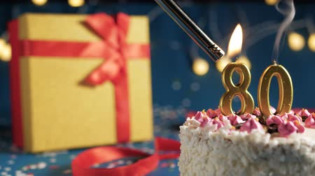 zapalovač : White birthday cake number 80 golden candles burning by lighter, blue background with lights and gift yellow box tied up with red ribbon. Close-up