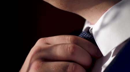 elevação : Male hand tighten tie. Caucasian man in white shirt and blue suit raises his chin tie several times. Close-up and Slow Motion Stock Footage