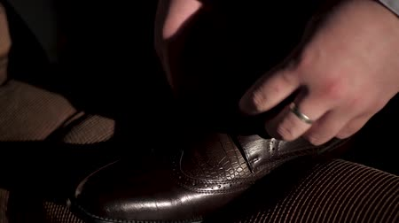 koronka : Male hand tie shoelaces. Caucasian man in white shirt and blue suit in dark room lace up shoes falling sunlight. Close-up and Slow Motion