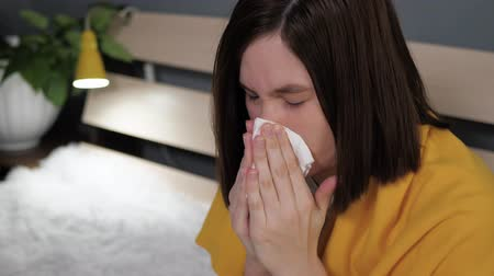 zsebkendő : Girl blows her nose. Attractive Caucasian woman blows her nose and wipes her nostrils with paper handkerchief. Cold, flu, runny nose, acute respiratory disease concept. Slow motion close up