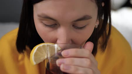 gorączka : Front view girl is drinking black tea. Attractive young woman is ill and drinks tea with lemon while sitting in bed. Cold, flu, sore throat, runny nose, acute respiratory disease concept. Slow motion