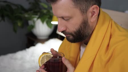 fájó : Guy is drinking black tea. Attractive young man is ill and drinks tea with lemon while sitting in bed. Cold, flu, sore throat, runny nose, acute respiratory disease concept. Slow motion close up