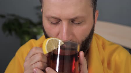 pléd : Front view guy is drinking black tea. Attractive young man is ill and drinks tea with lemon while sitting in bed. Cold, flu, sore throat, runny nose, acute respiratory disease concept. Slow motion Stock mozgókép