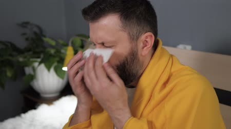 zsebkendő : Guy coughs. Attractive young caucasian man coughs intensively and covers her mouth with napkin. Cold, flu, sore throat, acute respiratory disease concept. Slow motion close up