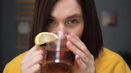 острый : Girl is drinking black tea and looking at camera. Attractive young woman is ill and drinks tea with lemon. Cold, flu, sore throat, runny nose, acute respiratory disease concept. Slow motion close up Стоковые видеозаписи