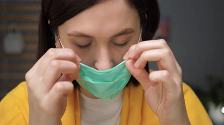 respiratory infection : Girl puts on respiratory mask. Attractive woman puts on face mask and looks at camera. Cold, flu, virus, tonsillitis, acute respiratory disease, quarantine, epidemic concept. Slow motion close up