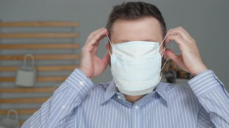 irony : Maximum protection for cold, flu, virus, acute respiratory infections, quarantine, epidemic, irony, sarcasm concept. Tired sick man puts on surgical mask, then one more and one more ... Stock Footage