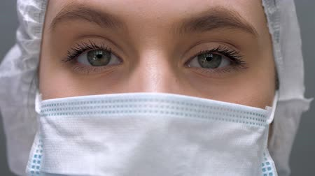 острый : Attractive girl in surgical mask looks at camera. Preparation for surgery, infection protection, quarantine, epidemic, medicine, virus, flu, acute respiratory infections concept. Close-up Slow Motion