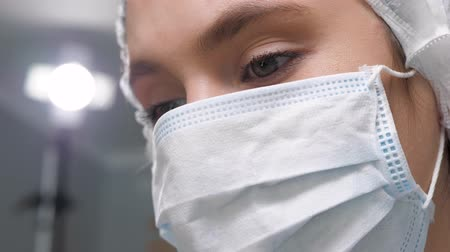 algılayıcı : Girl surgeon doctor in surgical mask looks down at patient and then to side at monitor or assistants. Operation, practitioner, operating room, surgery, transplantation, medicine concept. Close-up
