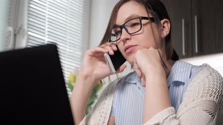 use laptop : Freelancer girl at work. Attractive young woman in glasses talking on phone in kitchen, looking at laptop, agrees with something said on mobile. Close-up Slow Motion Stock Footage