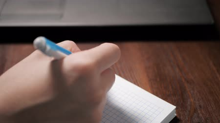 dokumentum : Female hand writes something in notebook with pen, next to it is laptop. Close-up Slow Motion