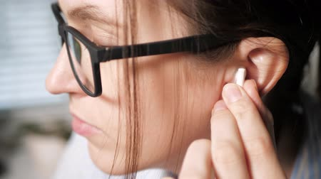 esquerda : Young girl with glasses puts on white earphone in her left ear. Listening to music concept. Close-up Slow Motion Stock Footage