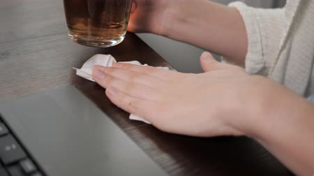 rozlití : Female hand wipes spilled liquid on wooden table with paper napkin, glass of tea in his right hand. Close-up Slow Motion Dostupné videozáznamy