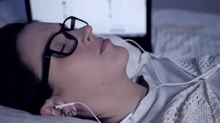 listens : Girl listens to music at night. Attractive young woman in glasses and headphones lies on bed next to laptop and enjoys listening to music. Close-up