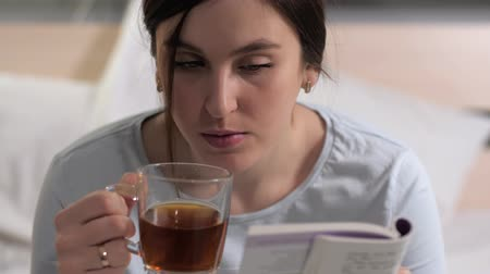 oturur : Girl is reading book. Young attractive caucasian woman sits in bed in evening and reads book and drinks black tea before bedtime. Close-up Stok Video