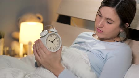 punctuality : Girl sets alarm clock. Young attractive woman alone in bedroom lies in bed, holds an alarm clock in her hands and sets small hand for six hours